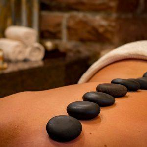 En kvinna ligger på mage med ryggen bar. På ryggen har man placerat ett antal lavastenar.