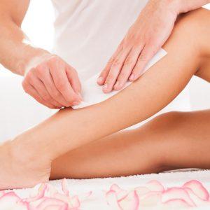 Man ser nedre benen av en kvinna. En skönhetsterapeut vaxer henne.